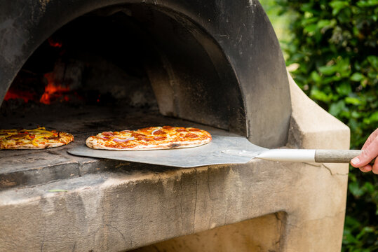 cooking pizza in an outdoor wood fired pizza oven