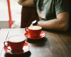 Two cups of coffee on a wooden table in a cafe with a man in the background
