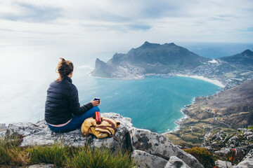 Hiker on a mountain summit enjoying the view and drinking coffee from a thermos flask
