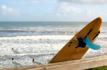 Yellow surfboard leaning on a fence with the Pacific ocean and surfers in the background