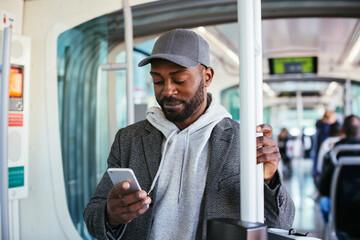 Black guy using smartphone in transport
