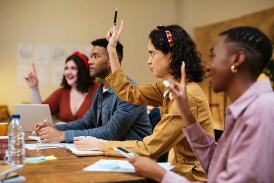 Multiracial coworkers having meeting and voting with raised hands