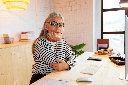 Smart senior lady at desk in office