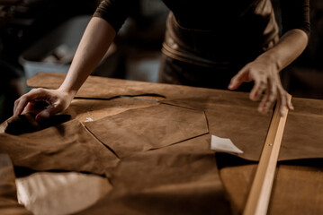 Woman puncturing leather