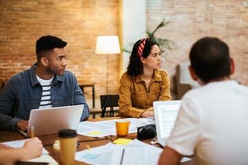 Modern freelance colleagues having meeting in loft workspace