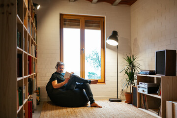 Man reading book in home library