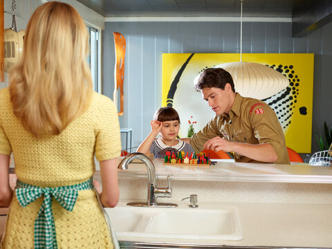 Vintage styled woman in kitchen and vintage styled man playing a board game with daughter in a mid century house.