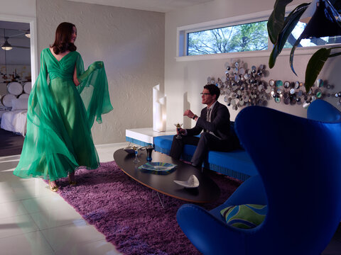 Vintage inspired woman with elegant flowing green dress standing in front of a man sitting on a couch in a mid century style home.