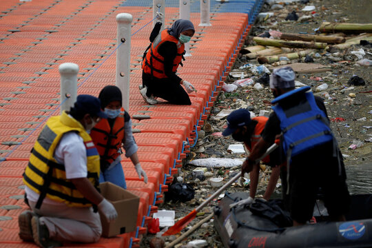 Members of enviromental group Bank Sampah Sungai Cisadane (Banksasuci) collect medical waste at Cisadane river in Tangerang