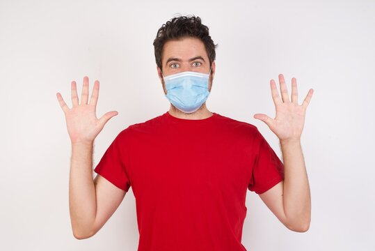 Optimistic Young caucasian man with short hair wearing medical mask  raises palms from joy, happy to receive awesome present from someone, shouts loudly, Excited caucasian male screaming.