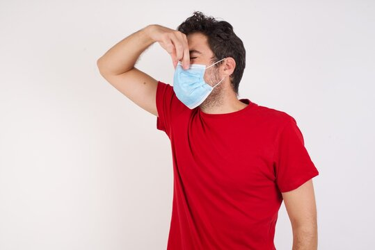 Young caucasian man with short hair wearing medical mask standing over isolated white wall smelling something stinky and disgusting, intolerable smell, holding breath with fingers on nose. Bad smell