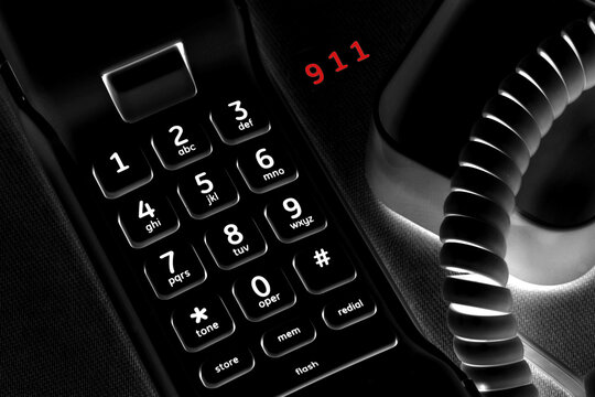 Ominous Concept of calling 911 with black phone and lit keys.  911 in red.