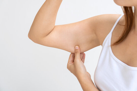 Young Asian woman pinching loose skin or flab on her upper arm
