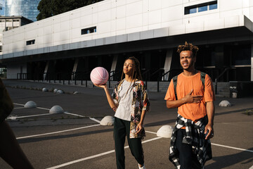 Teenage amazing african friends walking outdoors with ball