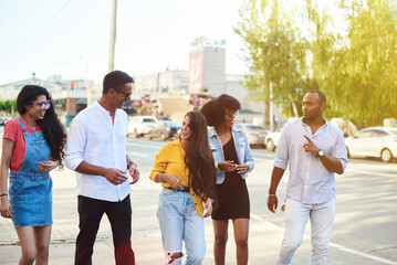 College students walking together outdoors. Young beautiful people of different nationalities walk around the city and talk