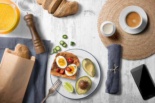 Top view breakfast scene with egg on toast, avocado and peppers, orange juice, coffee and sliced fresh bread on a whitewashed wooden counter