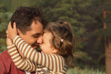 little happy daughter hugs daddy on sunny day