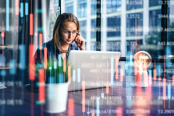 Businesswoman working at modern office.Technical price graph and indicator, red and green candlestick chart and stock trading computer screen background. Double exposure. Trader analyzing data