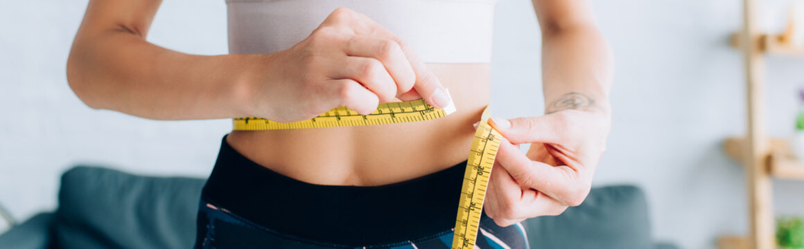 Panoramic crop of fit sportswoman measuring waist at home