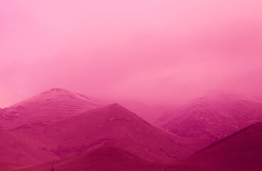 Beautiful shot of the hills covered in fog in a pink-tinted color