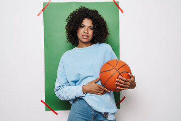 Image of young african american woman posing with basketball