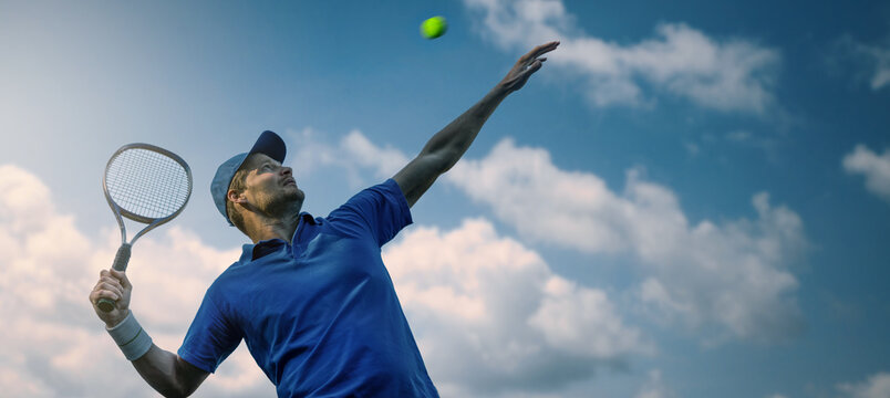 male tennis player hitting ball with racket against blue sky. banner copy space