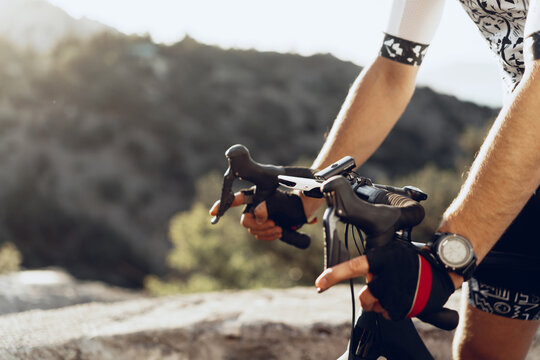 Hands of a professional cyclist in gloves on handle bar of a bicycle