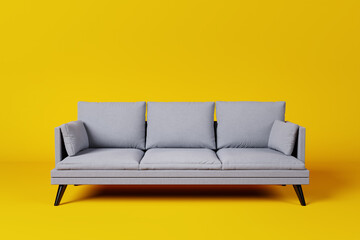 Grey couch with pillows on studio yellow background.