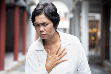 sick old senior woman suffering from GERD or acid reflux