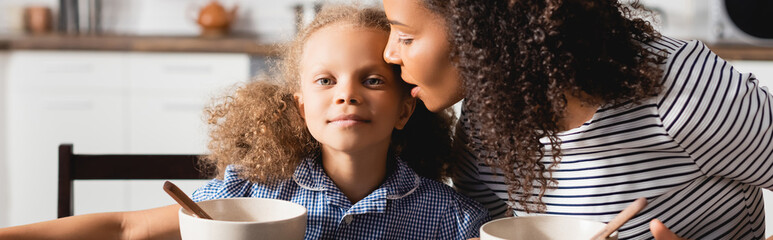 panoramic shot of woman in striped t-shirt whispering in ear of daughter during breakfast