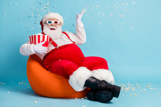 Full length photo of pensioner old man watch blockbuster throw popcorn make mess sit orange beanbag wear red santa x-mas costume suspender 3d glasses cap boot isolated blue color background