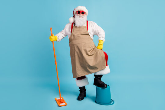Cleaning hero. Photo of pensioner old man grey beard hold mop leg bucket self-assured wear santa x-mas costume apron rubber glove suspender sunglass cap isolated blue color background