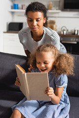young african american babysitter in striped t-shirt behind excited girl reading book on sofa