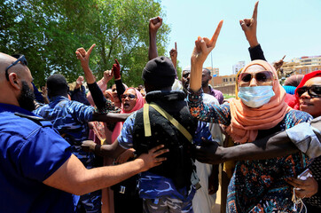 Sudanese citizens chant slogans outside the court during the new trial against ousted President Omar al-Bashir and some of his former allies, in Khartoum