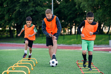 Two school boys are running ladder drills on the turf during football summer camp. Intense soccer...