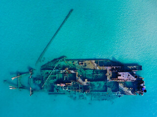Old shipwreck in blue clear sea. Aerial view of abandoned ship stranded ship in sea