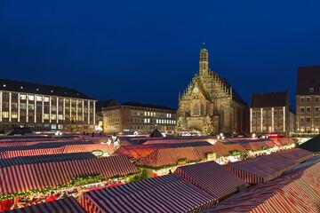 Nuremberg, Germany. Christkindlesmarkt Christmas market at Hauptmarkt platz (Main Market Square) in front of Frauenkirche (Church of Our Lady) in dusk.