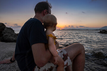 Father with his baby girl enjoying the sunset on the sea sitting near the rocks.