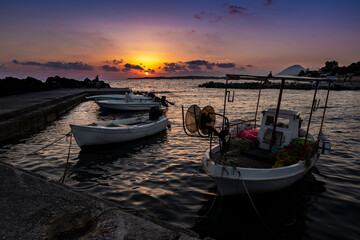 Stunning sunset on the adriatic sea with fisherman boats in the harbor on the foreground and the mountain on the background. Greece 2020