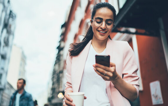 Joyful hipster girl enjoying network browsing during leisure time in urban town, happy Spanish blogger messaging with friends via modern smartphone using 4g wireless internet for web booking