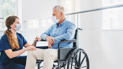 Caucasian nurse taking care of senior male patient on wheelchair in hospital. Young woman and old...