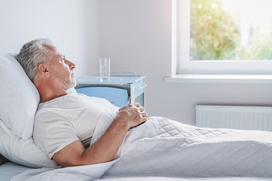 Side view of thoughtful senior male patient in hospital bed in ward room