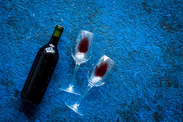 Fototapete - Wine bottle and glasses on blue background from above copy space