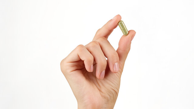 female hand holds in fingers capsule superfoods mooring or spirulina