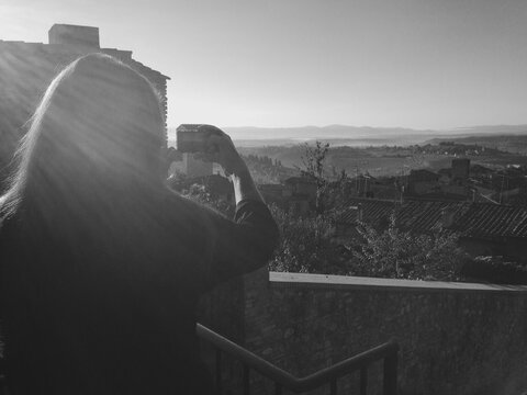 A woman taking a photograph of the scenic views of the beautiful Italian landscape at sunset