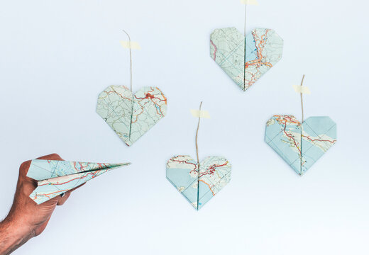 Travel concept: Origami plane with origami heart destinations