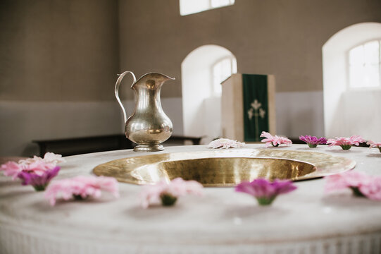 Flowers arranged around a Baptismal Font with Baptismal Pitcher