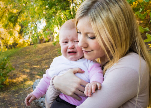 Mother's love and support for crying baby outdoors