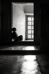 woman sitting in front of a window inside the taj mahal