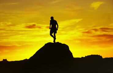 Mountain sunset with runner in silhouette on top of hill